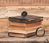 Stack of antique books with compass and magnifying glassl on woo — Stock Photo
