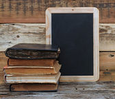 Old school books are stacked on a desk in front of a blackboard. — Stock Photo