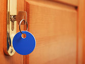 Key in keyhole with blank tag — Stock Photo