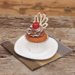 Cupcake with chocolate cream and cherry old wooden background — Stock Photo