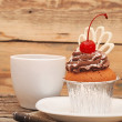 Cupcake with chocolate cream and cherry on old wooden background — Stock Photo