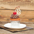 Stock Photo: Chocolate cherry cupcakes on old wooden background
