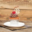 Chocolate cherry cupcakes on old wooden background — Stock Photo #15465011