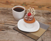 Chocolate cupcake with cherry and coffee cup — Stock Photo