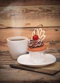 Pastel de chocolate de la placa blanca con una taza de café — Foto de Stock