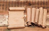 старый лист бумаги с ворсом прокручивает на старых деревянных фоне — Стоковое фото