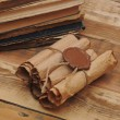 Pile of old books and scroll on wood background — Stock Photo