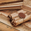 Pile of old books and scroll on wood background — Stok fotoğraf