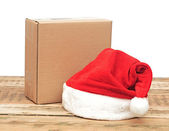 Santa hat with brown cardboard box over white — Stock Photo