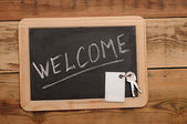 "Word ""welcome"" and key on small school wooden blackboard — Stock Photo"