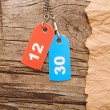 Two colorful tags with numbers on vintage background - Stock Photo