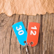 Two colorful tags with numbers on old paper - Stock Photo