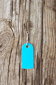 Blank blue tag on with silver chain old wooden background — Stock Photo