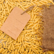 Pasta and price tag on sack burlap as background - Stock Photo