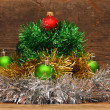 Christmas tree made of tinsel with christmas balls on a wooden t — Stock Photo