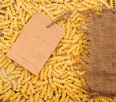 Pasta e cartellino del prezzo su tela sacco come sfondo — Foto Stock