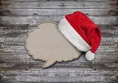 Bocadillo de diálogo en blanco papel reciclado con sombrero de santa en madera backgr — Foto de Stock