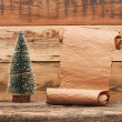 Stock Photo: Little toy christmas tree with old paper scroll