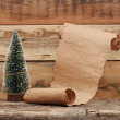 Little toy christmas tree with old paper scroll — Stock Photo