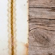 Old paper with beautiful ribbon on brown wood texture — Foto de Stock