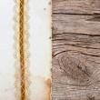 Old paper with beautiful ribbon on brown wood texture — Stock Photo