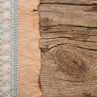 Old paper with beautiful ribbon on brown wood texture — Stockfoto #16866401