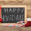 Handwritten happy holidays greeting on a small chalkboard with c — Stock Photo