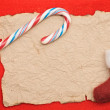 Red christmas background with blank paper sheet and candy cane — Stock Photo