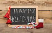 Handwritten happy holidays greeting on a small chalkboard with c — Stok fotoğraf