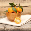 Bowl of fresh mandarins with leaf on wooden table - Foto Stock