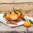Cinnamon and tangerines with leaves in a beautiful basket, on wo - Foto Stock
