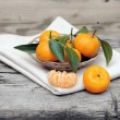 Tangerines with leaves in a beautiful basket on wooden table - Photo