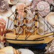 Model classic boat on sea shells background  — Stock Photo