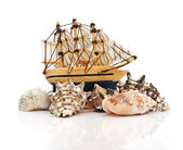 Model classic boat on sea shells — Stock Photo