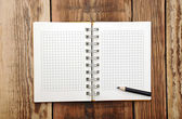 A open note book with pencil on a wooden desk — Stock Photo