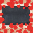 Foto de Stock  : Blank chalkboard over Valentine hearts background