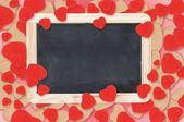 Blank chalkboard over Valentine hearts background — Stock Photo