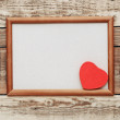 A red heart in an old wooden frame on an old rough wall. — Stock Photo #19487381