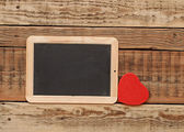Small blackboard with a red heart on wooden wall — Stock Photo