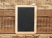 Blackboard on the wood wall. — Stock Photo