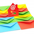 Red plastic house shaped object on colorful envelopes white back — Stock Photo