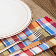 Empty plate with fork and knife on wooden table — Stock Photo