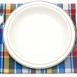 The knife, fork and white plate on a colorful napkin on a white — Stock Photo