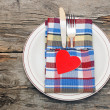 Cutlery in the colorful napkin and red heart on an empty plate — Stock Photo