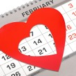 Red heart shape marker on calendar page showing February 14 Vale - Stock Photo