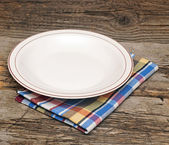 Empty plate on tablecloth on wooden table — Stock Photo