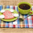 Tea cup with sweet heart shaped cookie on colorful napkin — Stock Photo
