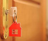 Symbol domu a držet klíč v klíčové dírky — Stock fotografie