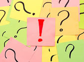 An exclamation mark among question marks — Stock Photo