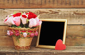 Bouquet paper flower in a basket with blank photoframe — Stock Photo
